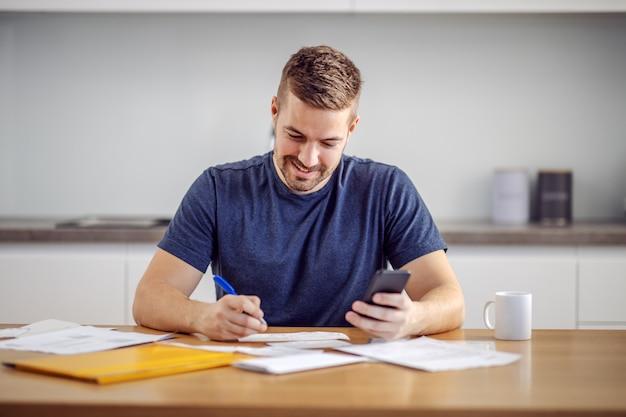 Jovem bonito sorridente barbudo homem sentado em casa, calculando o orçamento e preenchendo as contas.
