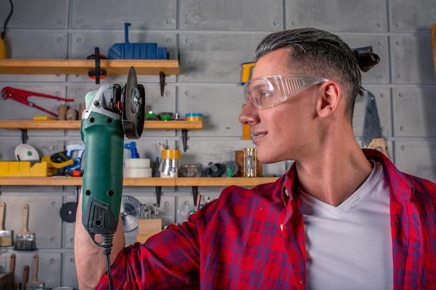 Jovem bonito sorridente carpinteiro caucasiano, segurando uma serra circular nas mãos na oficina. pronto para trabalhar