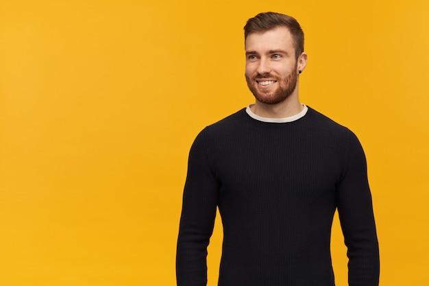 Jovem bonito sorridente com barba e manga comprida preta em pé e olhando para o lado por cima da parede amarela