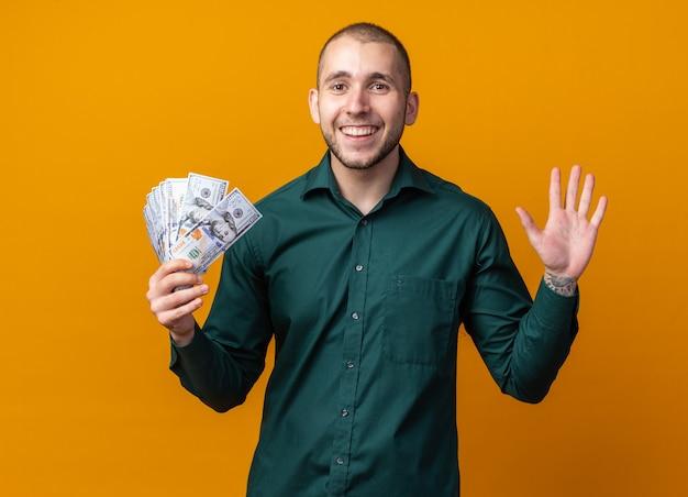 Jovem bonito sorridente com uma camisa verde segurando dinheiro e mostrando cinco