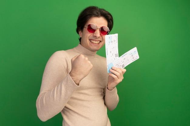 Jovem bonito sorridente de óculos segurando ingressos e mostrando um gesto de sim isolado na parede verde