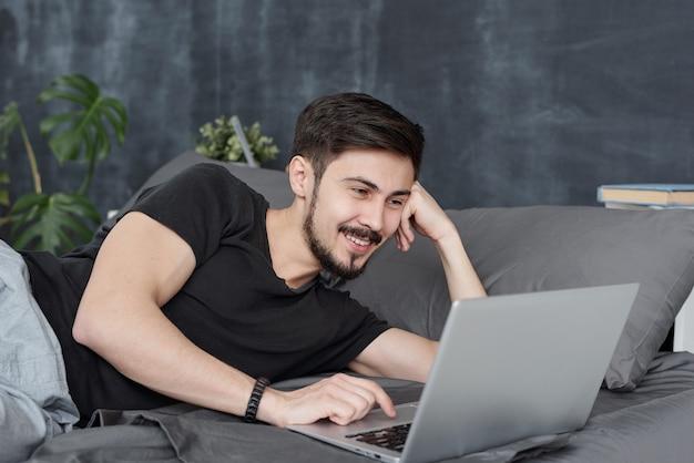 Jovem bonito sorridente, deitado na cama e usando o laptop enquanto se diverte com amigos via aplicativo online
