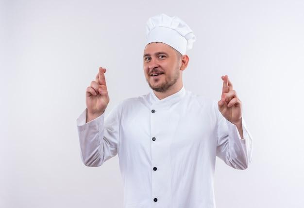Jovem bonito sorridente em uniforme de chef fazendo gesto de dedos cruzados isolado no espaço em branco