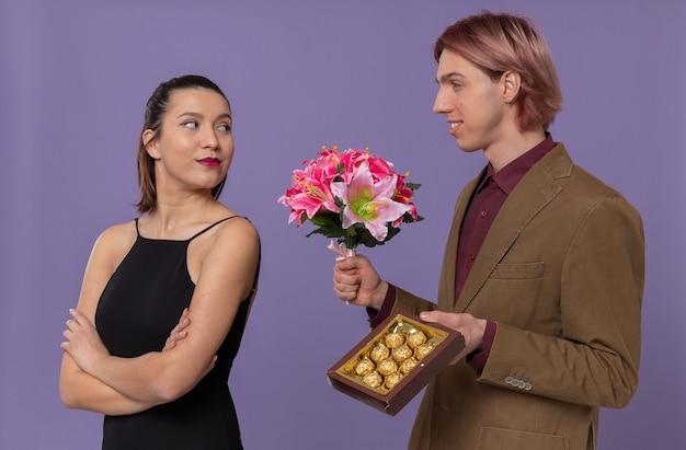 Jovem bonito sorridente segurando um buquê de flores e uma caixa de chocolate, olhando para uma bela jovem
