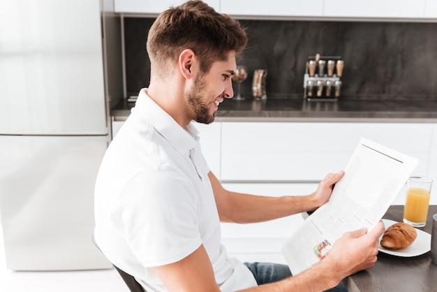 Jovem bonito sorridente tomando café da manhã e lendo jornal na cozinha