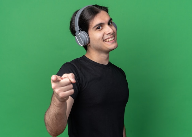 Jovem bonito sorridente usando camiseta preta e fones de ouvido, mostrando seu gesto isolado na parede verde