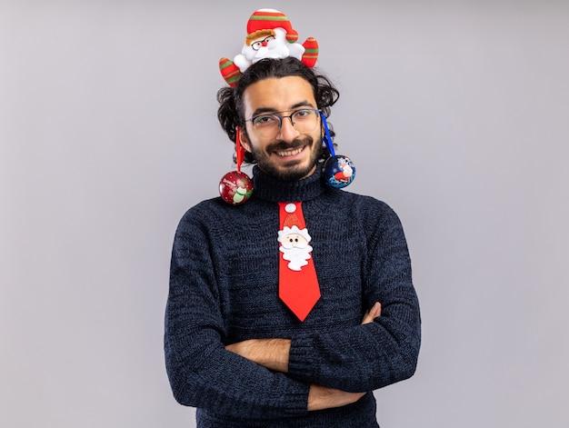 Jovem bonito sorridente usando gravata de natal com aro de cabelo pendurado bola de natal nas orelhas cruzando as mãos isoladas