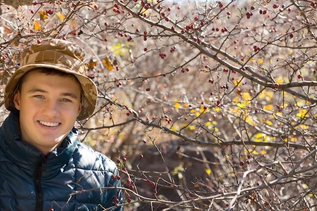 Jovem bonito sorridente usando um chapéu e um sobretudo quente, posando ao ar livre em uma floresta de outono, olhando para a câmera com um sorriso amigável