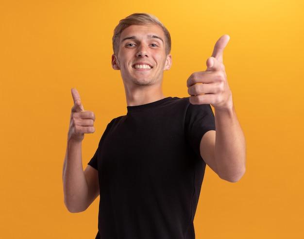 Jovem bonito sorridente usando uma camisa preta, mostrando um gesto isolado na parede amarela