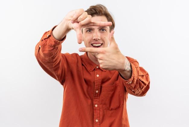 Jovem bonito sorridente usando uma camisa vermelha e mostrando um gesto com uma foto
