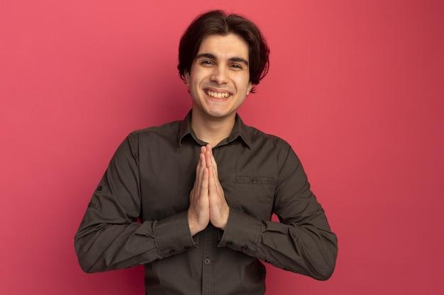 Jovem bonito sorridente usando uma camiseta preta e mostrando um gesto de coração isolado na parede rosa