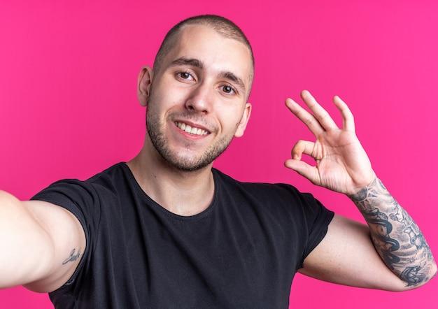 Jovem bonito sorridente usando uma camiseta preta e mostrando um gesto de ok isolado na parede rosa
