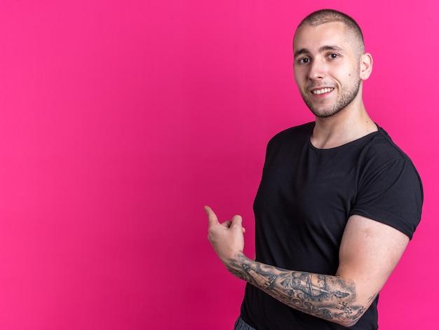 Jovem bonito sorridente vestindo camiseta preta apontando para trás, isolado na parede rosa com espaço de cópia