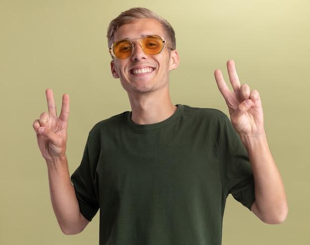 Jovem bonito sorridente, vestindo uma camisa verde com óculos, mostrando um gesto de paz isolado em uma parede verde oliva