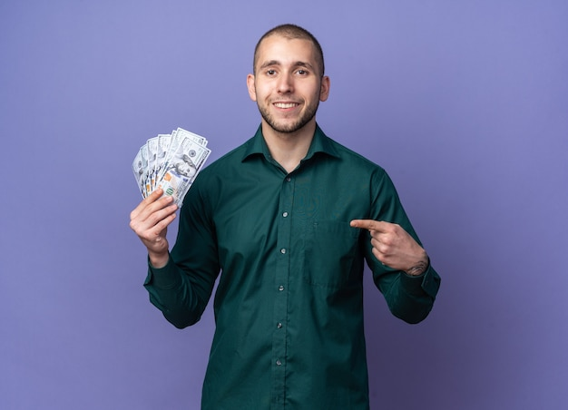 Jovem bonito sorridente, vestindo uma camisa verde segurando e apontando para o dinheiro