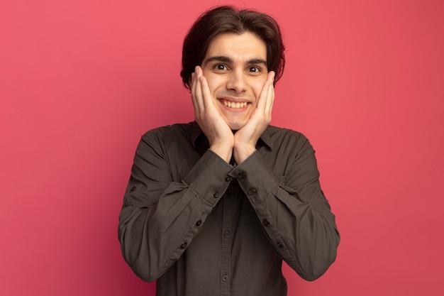 Jovem bonito sorridente, vestindo uma camiseta preta e colocando as mãos nas bochechas isoladas na parede rosa
