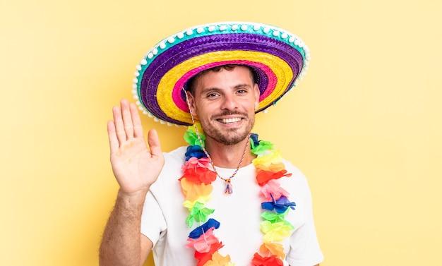 Jovem bonito sorrindo alegremente, acenando com a mão, dando as boas-vindas e cumprimentando você. conceito de festa mexicana