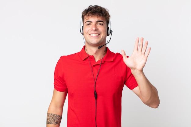 Jovem bonito sorrindo alegremente, acenando com a mão, dando as boas-vindas e cumprimentando você. conceito de telemarketing