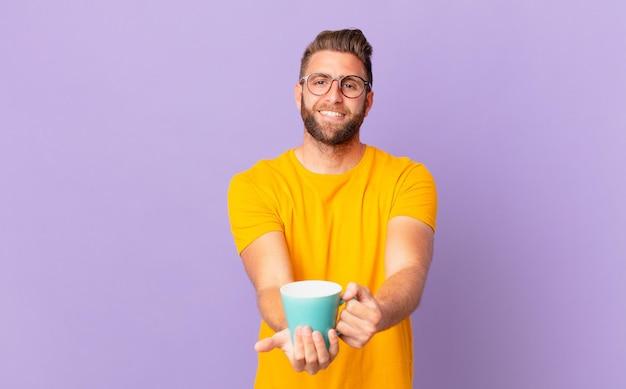 Jovem bonito sorrindo alegremente com simpáticos e oferecendo e mostrando um conceito. e segurando uma caneca de café