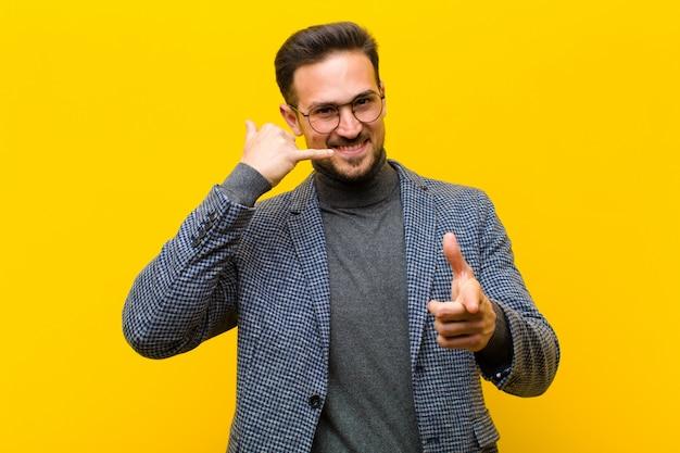 Jovem bonito sorrindo alegremente e apontando para a câmera enquanto faz uma ligação você mais tarde gesto, falando na parede do telefone laranja