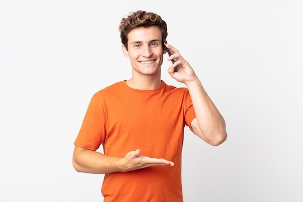 Jovem bonito sorrindo alegremente, sentindo-se feliz e mostrando um conceito e falando com um telefone inteligente