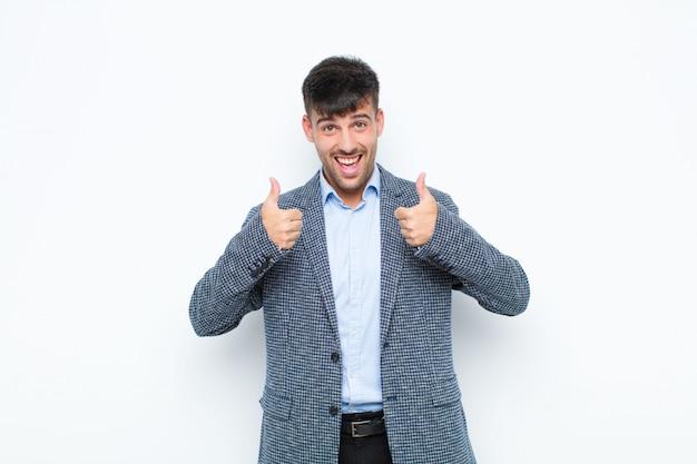 Jovem bonito sorrindo amplamente olhando feliz, positivo, confiante e bem sucedido, com os dois polegares contra a parede branca