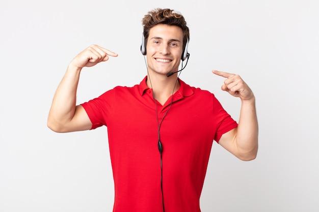 Jovem bonito sorrindo com confiança, apontando para o próprio sorriso largo. conceito de telemarketing