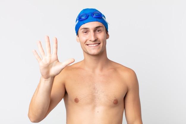 Jovem bonito sorrindo e parecendo amigável, mostrando o número cinco. conceito de nadador