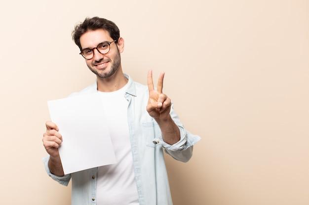Jovem bonito sorrindo e parecendo amigável, mostrando o número dois ou o segundo com a mão para a frente, em contagem regressiva