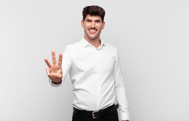 Jovem bonito sorrindo e parecendo amigável, mostrando o número três ou o terceiro com a mão para a frente, em contagem regressiva