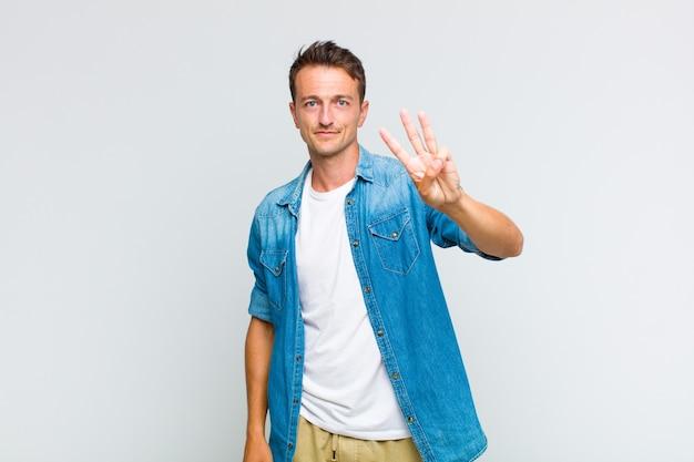 Jovem bonito sorrindo e parecendo amigável, mostrando o número três ou terceiro com a mão para a frente, em contagem regressiva