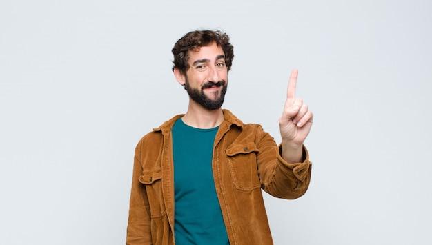 Jovem bonito sorrindo e parecendo amigável, mostrando o número um ou o primeiro com a mão para a frente, em contagem regressiva contra uma parede plana
