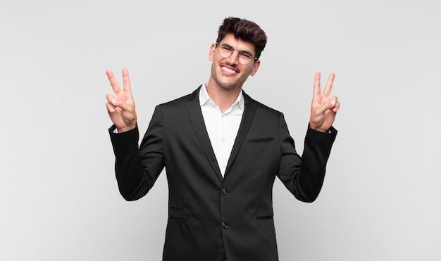 Jovem bonito sorrindo e parecendo feliz, amigável e satisfeito, gesticulando vitória ou paz com as duas mãos