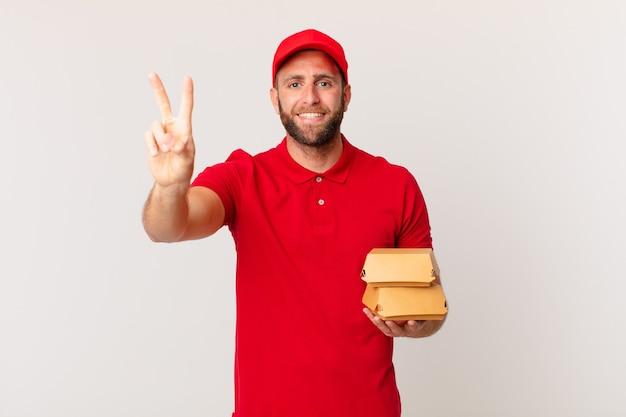 Jovem bonito sorrindo e parecendo feliz, gesticulando vitória ou hambúrguer da paz