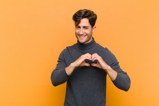 Jovem bonito sorrindo e se sentindo feliz, fofo, romântico e apaixonado, fazendo formato de coração com as duas mãos sobre a parede laranja