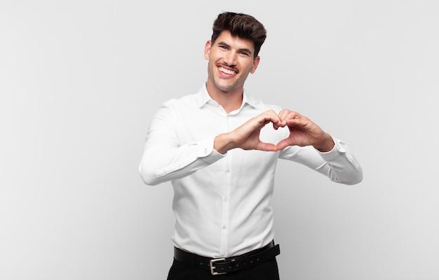 Jovem bonito sorrindo e se sentindo feliz, fofo, romântico e apaixonado, fazendo formato de coração com as duas mãos