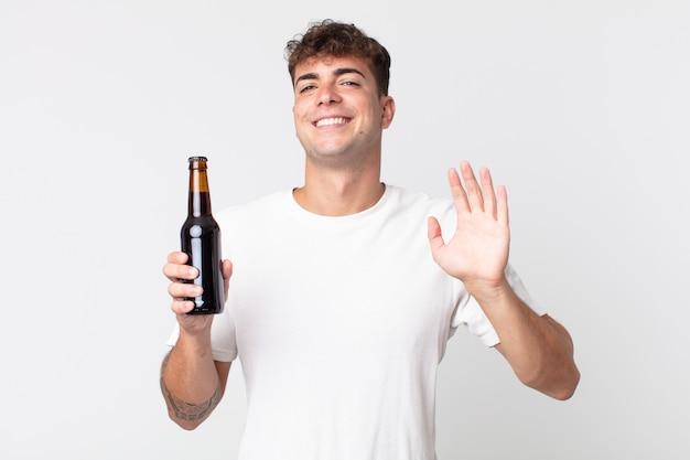 Jovem bonito sorrindo feliz, acenando com a mão, dando as boas-vindas, cumprimentando você e segurando uma garrafa de cerveja
