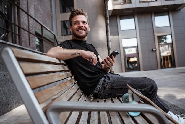 Jovem bonito sorrindo olhando para alguém enquanto usa o smartphone, curtindo postagens, compartilhando conteúdo de novo, com longboard em pé por perto enquanto descansava sentado no banco usando roupa casual