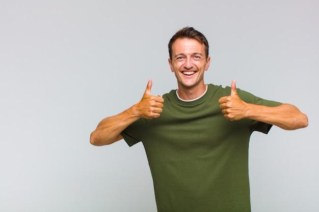 Jovem bonito sorrindo, parecendo feliz, positivo, confiante e bem-sucedido, com os dois polegares para cima