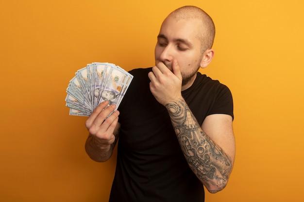Jovem bonito surpreso com uma camisa preta, segurando e olhando para o dinheiro cobrindo a boca com a mão