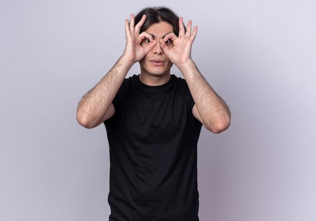 Jovem bonito surpreso com uma camiseta preta e um gesto de olhar isolado na parede branca
