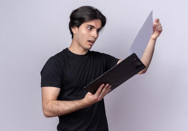 Jovem bonito surpreso com uma camiseta preta folheando a prancheta isolada na parede branca
