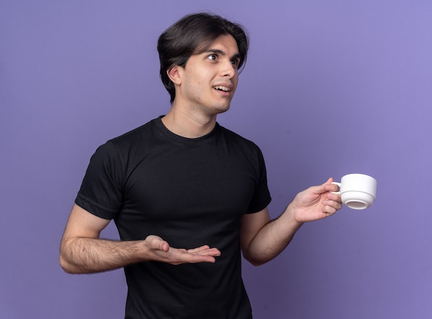 Jovem bonito surpreso com uma camiseta preta segurando e apontando com a mão para uma xícara de café isolada na parede roxa