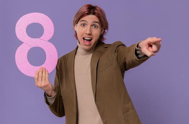 Jovem bonito surpreso segurando o número oito rosa e apontando para o lado