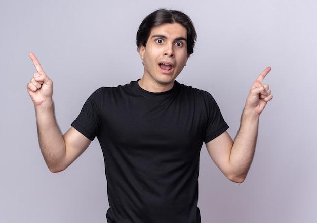 Jovem bonito surpreso usando a camiseta preta com pontas em lados diferentes, isolados na parede branca