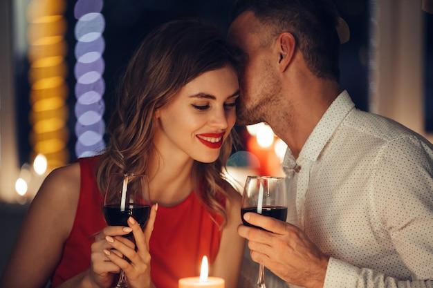 Jovem bonito sussurrar para sua mulher enquanto jantar romântico