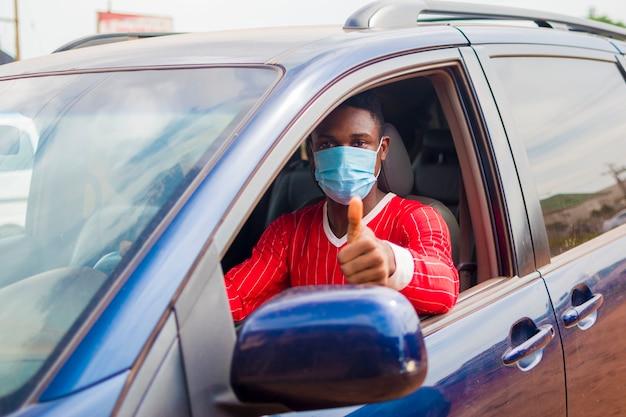 Jovem bonito taxista africano usando máscara facial prevenindo, prevenindo, prevenindo-se do surto na sociedade e fazendo sinal de positivo