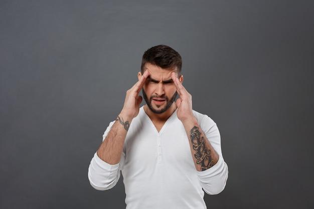 Jovem bonito tem dor de cabeça ao longo da parede cinza