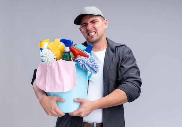 Jovem, bonito, tenso, cara de limpeza vestindo camiseta e boné, segurando um balde com ferramentas de limpeza isolado na parede branca