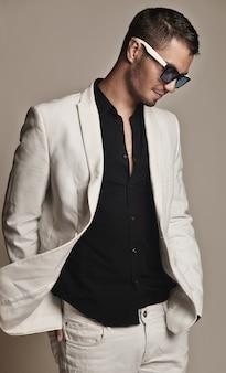 Jovem bonito terno branco com óculos de sol na moda